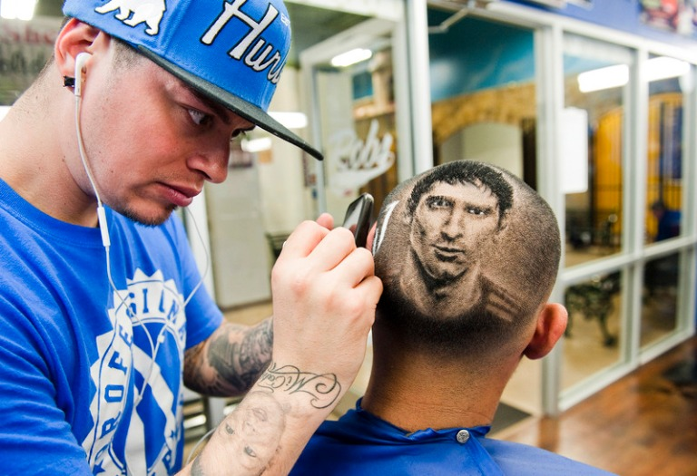 Ferrel cuts the likeness of Messi on the head of customer Hernandez at his barbershop in San Antonio