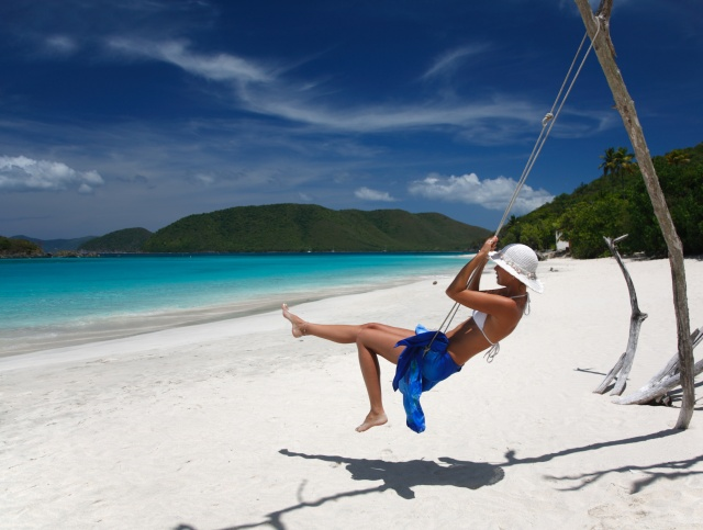 woman on a swing at tropical beach in the caribbean